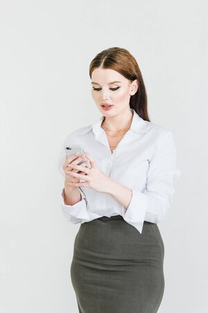 A business woman in a skirt and blouse with a mobile phone in her hands performs management work