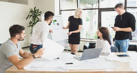 The working process. Casually dressed employees in the process of discussion of the project are bright and spacious office Stock Photo