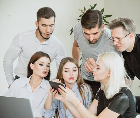 A company of young people having a meeting and watching information on a tablet PC Stock Photo