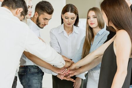 Company of young employees Low Angle View Stacking Hands Together in office Stock Photo