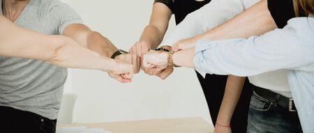 Many fists of a group of people showing team connection
