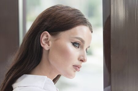Bored business lady with beautiful blue eyes is leaning by office window looking to the street Stok Fotoğraf