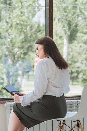 Young beautiful woman in a business suit is sitting by the office window In her hands a tablet computer She looks in its reflection like in a mirror. Stock Photo