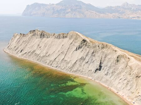CRIMEA AUGUST 2019 Chameleon cape in Koktebel bay Cape changing a color depends day time Aerial view