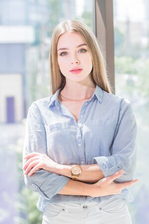 portrait of a young beautiful woman with arms folded under her chest against the window Stock Photo
