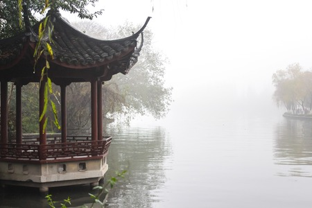 Traditional Chinese gazebo on a lake in the fog Stock Photo