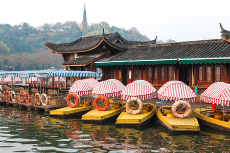 Boat rental parking. Boat station in Chinese style with spoons and catamarans, in the background of the mountain