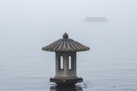 Lantern on the lake in the fog. Traditional chinese lantern on the West Lake in Hangzhou. Misty landscape