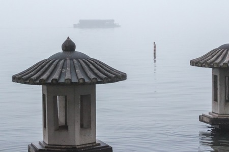 city park boat house: Lantern on the lake in the fog. Traditional chinese lantern on the West Lake in Hangzhou. Misty landscape