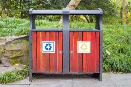 Trash bins with sorting signs in the park on grass background Stock Photo