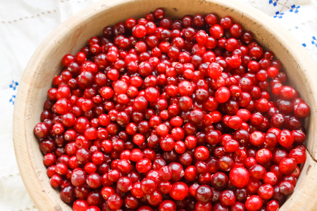 Red berries close-up. Top view of red berries in a wooden bowl