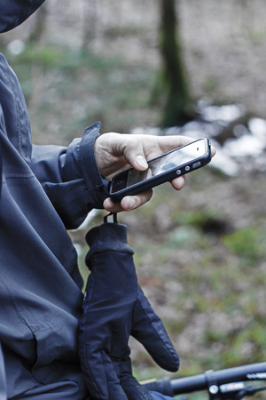 Man hand holding smart phone in the forest 写真素材