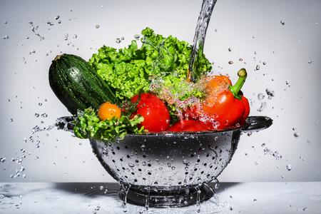 vegetables in a colander under running water 스톡 콘텐츠