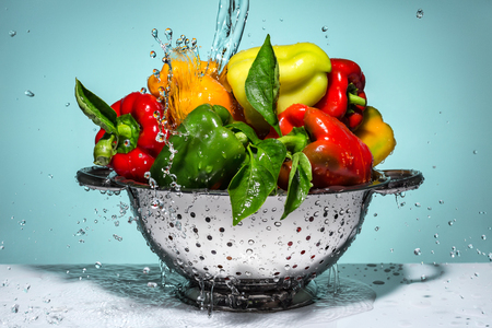 colander: Peppers of different colors in a colander under running water