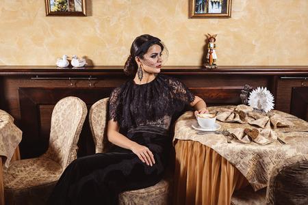 traje de gala: Se�ora en vestido de noche en la mesa en un caf�