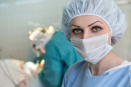female eyes: Nurse in mask in the operating room