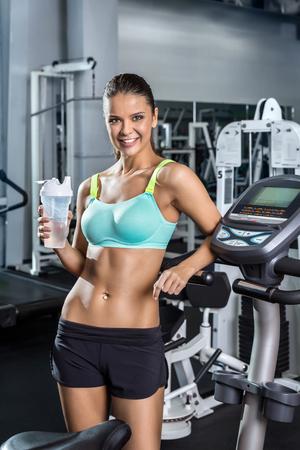 ejercicio aeróbico: Chica con un vaso de agua en el gimnasio