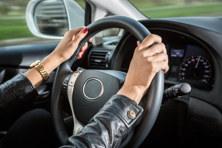 Woman's hands on the steering wheel of the car 스톡 콘텐츠