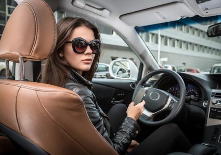 femme brune sexy: Fille dans des lunettes de soleil de conduire une voiture