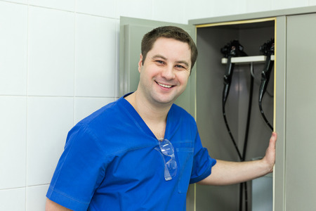 Doctor near cabinet with drying endoscope