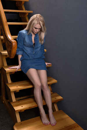 women legs: Thoughtful blonde woman sitting on wooden stairs Stock Photo