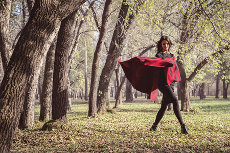 Model in autumn park with a red stole Stockfoto