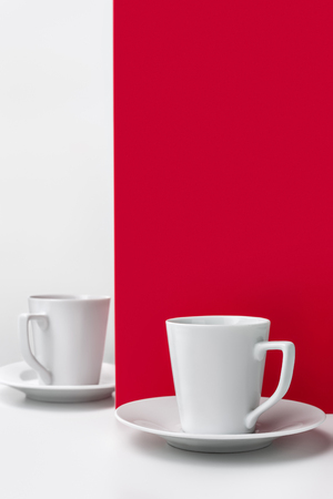 Two cups of coffee on red with a clean background for notes