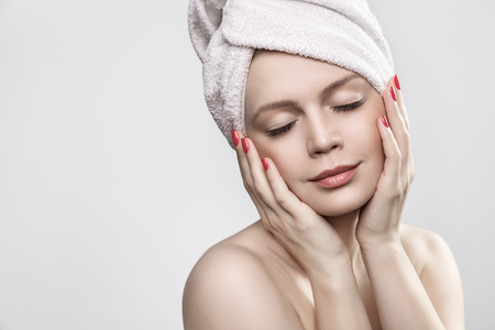 a bathing place: Sensual woman in white towel, eyes closed Stock Photo
