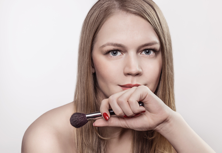 Brush for make-up in girls hand.