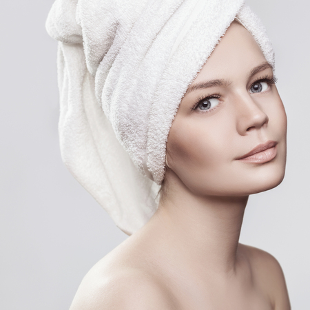 a bathing place: Close-up portrait of young woman with perfect healthy skin and bath towel on head. Isolated on white Stock Photo