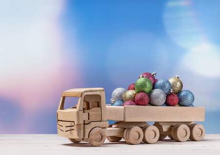 Toy wooden car with christmas balls in back.