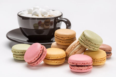Black cup of coffee with mini-white marshmallows, colorful French macaroons.