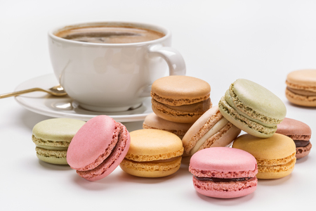 Multicolored macaroons and coffee with foam.