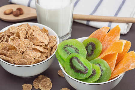 Breakfast. Bowls with cornflakes, dried kiwi and mango. Glass of milk. Healthy eating. Stock Photo