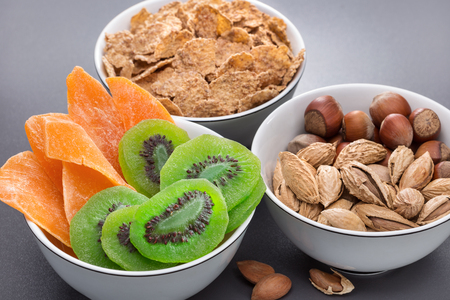 Breakfast. Three bowls of nuts, cornflakes, dried kiwi and mango. A glass of milk. Healthy eating. Stock Photo