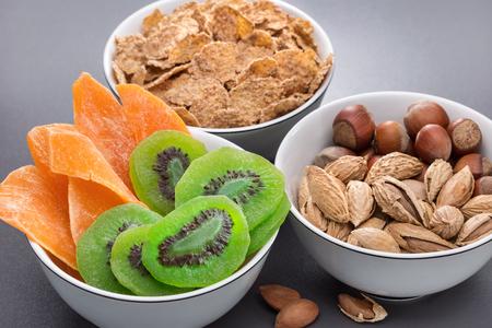 Breakfast. Three bowls of nuts, cornflakes, dried kiwi and mango. A glass of milk. Healthy eating. Standard-Bild