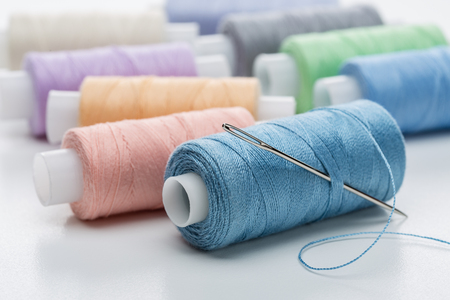 Many coils with threads of pastel tones. Coil of blue threads with large needle.