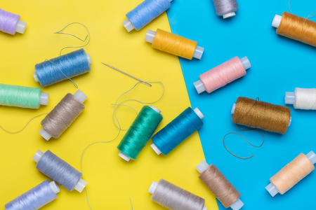 Many coils with multi-colored threads, needle on yellow and blue background. 写真素材