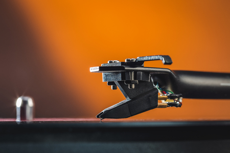 Close up macro photography to phono cartridge on tonearm of vintage analog hi fi stereo vinyl turntable with copy space.