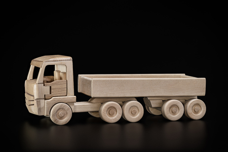 Toy, car with trailer. Reflection of truck on dark surface.
