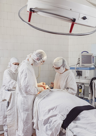 Operating room. Surgeon and assistant perform surgery on patient´s jaw.