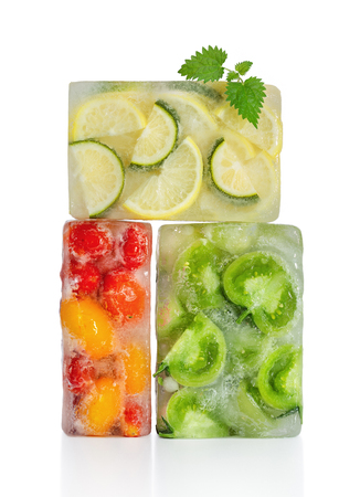 Frozen food concept: red, yellow and green tomatoes, lemon and lime were frozen inside ice cubes. Standard-Bild - 116492141