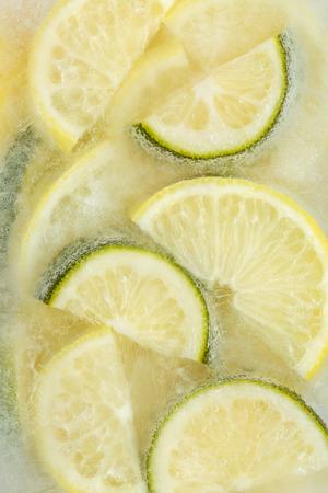 Fresh lemons and lime slices frozen in ice cube on white background. Studio shot. Standard-Bild - 116492143