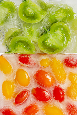 Fresh red, yellow tomatoes and green tomato slices frozen in ice cube on white background. Studio shot. Standard-Bild - 116492151