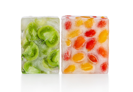Fresh red, yellow tomatoes and green tomato slices frozen in ice cube on white background. Studio shot.
