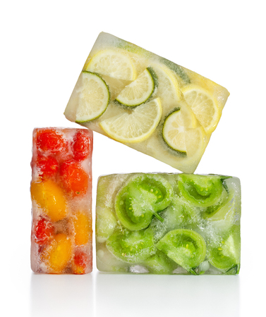 rozen food concept: red, yellow and green tomatoes, lemon and lime frozen inside ice cubes. Standard-Bild - 116492154