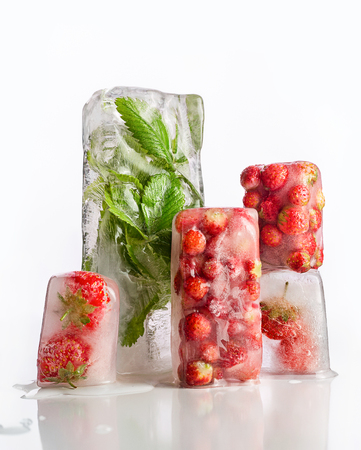 Frozen strawberries. Green berry leaves in ice cube. Standard-Bild - 116492182
