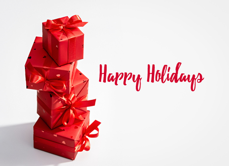 Happy holidays. Set of vertically arranged red boxes with gifts. Stock Photo