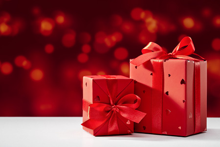 Surprise in red box with bow on bokeh background. Festive design, on white table. Copy space.