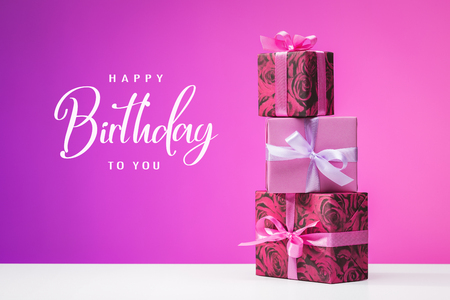 Happy Birthday. Set of vertically arranged multi-colored boxes with gifts. Fuchsia background. Festive events.